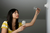 Montreal (Qc) CANADA, July 24, 2007 - Model Released photo- A young asian woman replace an incandescent light bulb by an efficient compact fluorescent light bulb.(CFL)<br />