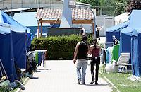 Una coppia cammina in una tendopoli a Paganica, nei pressi dell'Aquila, 8 giugno 2009, poco piu' di due mesi dopo il sisma che ha sconvolto l'Abruzzo..A couple walks in a tent city in Paganica, near L'Aquila, 8 june 2009, about 2 months after the earthquake that hit the Abruzzo region in central Italy..UPDATE IMAGES PRESS/Riccardo De Luca