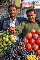 India, Dehradun.  Fruit Vendor offering the Photographer a Pomegranate.