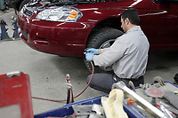 File Photo<br /> <br /> Safety at work in a body shop - A worker wearing all safety devices does sanding and body work on a car.