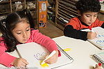 Education preschool 4 year olds art activity boy and girl sitting side by side drawing with markers girl using left hand and boy using right hand