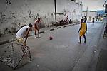 Young boys playing football in the street in Santiago de Cuba.