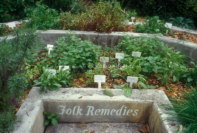 Tiered raised bed herb garden arranged by category and sign plant labels: Folk Remedies. Anise Hyssop, Lemon Balm, Yarrow, Arugula, Dill, Thyme, Calendula, Horehound