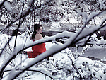 Beautiful woman in red kimono with bare shoulders sitting on snow in a beautiful snowy winter nature scenery by a river Image © MaximImages, License at https://www.maximimages.com