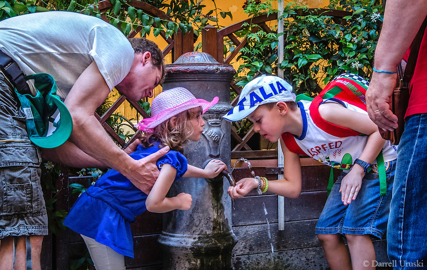 "Urban Street Photography of two children capturing a drink from one of the many water fountains in Rome. The Nasoni, water fountain which translates as ""big noses,"" are spread all over the city of Rome. <br />