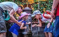 """Urban Street Photography of two children capturing a drink from one of the many water fountains in Rome. The Nasoni, water fountain which translates as """"big noses,"""" are spread all over the city of Rome. <br /> The ITALIA, cap, and colours on his backpack really add character to this traditional Italian scene."""