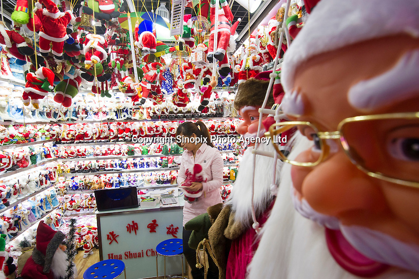 November 27, 2015, Yiwu China - A vendor arranges cheap Christmas decorations inside a stall in the Festival Arts section of Arts of Crafts inside the Yiwu International Trade Market. Yiwu International Trade Market is the world's largest whole sale market for small commodities. Christmas decorations are available for bulk purchase all the year round.Photo by Dave Tacon / Sinopix