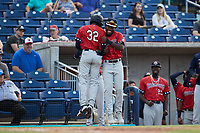 Johan Lopez (32) of the Charleston RiverDogs celebrates with teammate Osleivis Basabe (9) after hitting a home run against the Kannapolis Cannon Ballers at Atrium Health Ballpark on June 30, 2021 in Kannapolis, North Carolina. (Brian Westerholt/Four Seam Images)