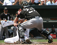 Ramon Castro #27 of the Chicago White Sox tags out Jake Fox #9 of the Baltimore Orioles at home plate during a MLB game at Camden Yards, on August 8 2010, in Baltimore, Maryland.