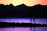 two adults practicing tai chi at sunset, silhouetted against dramatic water and mountain scene