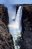 Victoria Falls, Zambia to Zimbabwe border. The Falls through the canyon with rainbow.