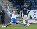 Falkirk's Rory Loy is challenged by Queen of the South's Kevin Holt.