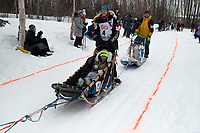 Kristy Berington and team run past spectators on the bike/ski trail near University Lake with an Iditarider in the basket and a handler during the Anchorage, Alaska ceremonial start on Saturday, March 7 during the 2020 Iditarod race. Photo © 2020 by Ed Bennett/Bennett Images LLC
