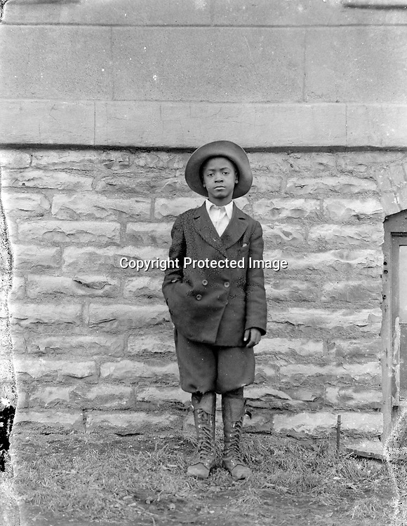 """BESIDE THE CHURCH. The wall behind this young man, who poses so confidently, appears to be Mount Zion Baptist Church. That African American congregation was Lincoln's second black church when founded in 1879. The congregation built a stone """"basement church"""" in 1892 on a building site received from the Nebraska legislature in 1883. The stuccoed main story of the church was not added until 1922-1925.<br /> <br /> <br /> Photographs taken on black and white glass negatives by African American photographer(s) John Johnson and Earl McWilliams from 1910 to 1925 in Lincoln, Nebraska. Douglas Keister has 280 5x7 glass negatives taken by these photographers. Larger scans available on request."""