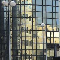 A part of a modern building with a mirroring glass wall that reflects another one, with two street lamps (Paris, 2007).<br /> <br /> Una parte di un edificio moderno dalla parete di vetro a specchio che ne riflette un altro, con due lampioni (Parigi, 2007).