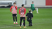 Referee, Jeremy Simpson takes a knee ahead of kick-off together with the Sheffield Wednesday players while Brentford players have opted to stand during Brentford vs Sheffield Wednesday, Sky Bet EFL Championship Football at the Brentford Community Stadium on 24th February 2021