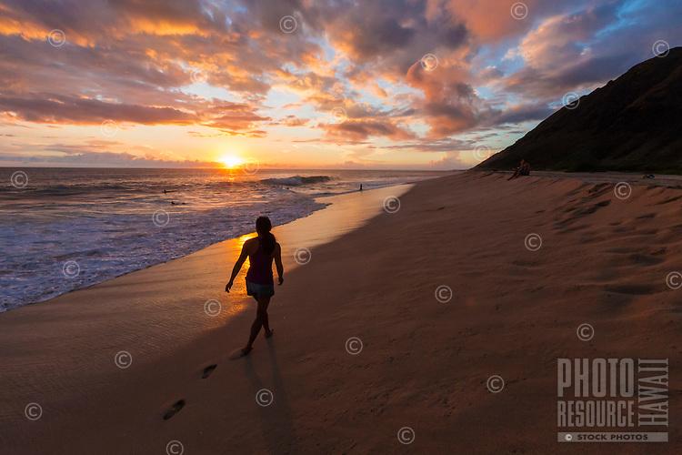 A woman enjoys the beautiful sunset while strolling along the beach at Yokohama Bay, West O'ahu.