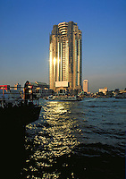The Peninsula. The last of the mid 90's construction boom in Bangkok, Thailand. Viewed from a distance over the water, sunset reflecting off the building and water. Bangkok, Thailand.