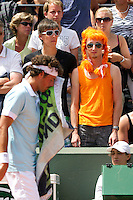 24-05-11, Tennis, France, Paris, Roland Garros, A Dutch supporter with orange wig looks on while Robin Haase passes by