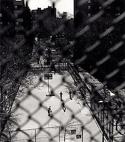 People playing basketball seen through chain link fence<br />