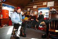 Wednesday March 7, 2007   ----  Martin Buser takes a coffee break insdie the cabin while on his 24 hour layover at Ophir.