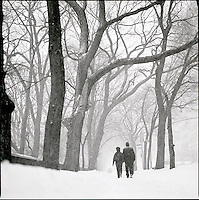 Couple walking through snowstorm on upper 5th Avenue<br />