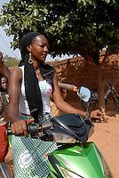 BURKINA FASO Bobo Dioulasso, old town, young modern woman with scooter / Burkina Faso Bobo-Dioulasso , Frau mit Motorroller