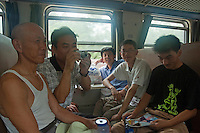 Men travelling by passenger train going from Beijing to Datong, China.