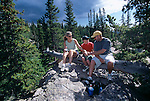 Family of three hikers snack while sitting on a log near Dream Lake in Rocky Mtn Nat'l Park, CO.