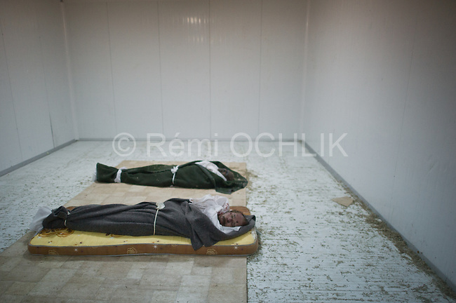 Remi OCHLIK/IP3 - Misrata : GRAPHIC CONTENT.The corpses of Libya's ex-strongman Moamer Kadhafi (middle) and his son Mutassem (first) are pictured on mattresses inside the cold storage room of a vegetable market near a mosque on the outskirts of Misrata on October 23, 2011. Military commanders in the Libyan city of Misrata said that no post-mortem would be carried out on the body of Kadhafi despite concerns over how the toppled dictator died