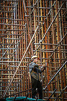 A construction worker operates on a lattice of scaffoldings under an highway construction site in Shanghai, China..