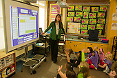 MR / Schenectady, NY. Zoller Elementary School (urban public school). Kindergarten inclusion classroom. Teacher and her students use digital whiteboard at calendar time. Students raise their hands in response to her question. This is part of a daily routine to help reinforce basic concepts about time by frequent repetition. MR: War15. ID: AM-gKw. © Ellen B. Senisi.