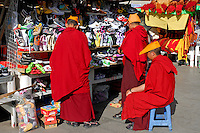 "Tibetan monks of the Gelug ""Yellow Hat"" sect, buying footware at market stall on the Barkhor pilgrim route, Lhasa, Tibet."