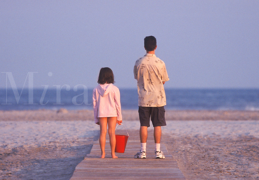 A brother and sister stand on the ocean beach looking at the ocean waves and preparing to play in the sand.