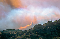 870000363 a los angeles county fire fighting helicopter flying through thick smoke performs an aerial retardant drop on a burning hillside in the path of the topanga fire in the hills above the san fernando valley in southern california