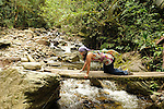 In Colombia, a young woman hiker crosses a precarious timber bridge in Acaime Nature Reserve in Colombia's enchanting Valle de Cocora. The hike passes from green grasslands and a warm climate, through dense, semi-tropical jungle, and finally to cool, breezy mountain vistas at around 3,000 meters.