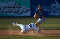 Ryan Dudney (15) of the Queens Royals slides into second base as Hunter Pearre (14) of the Barton Bulldogs gets the force out at Intimidators Stadium on March 19, 2019 in Kannapolis, North Carolina. The Royals defeated the Bulldogs 6-5. (Brian Westerholt/Four Seam Images)