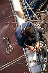 A sailor fixes a rope while sitting on yard high above the Atlantic Ocean
