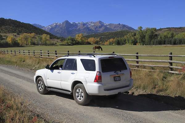 White SUV on dirt road with Sneffels Range behind, San Juan Mountains, autumn, Colorado.