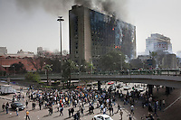 The ruling National Democratic party building burns the morning after being set on fire as protesters gather beneath. Continued anti-government protests take place in Cairo calling for President Mubarak to stand down. After dissolving the government, Mubarak still refuses to step down from power. .