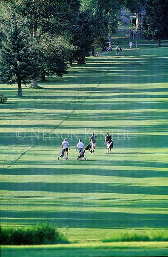 Golfers walk down the fairway on a summer evening in Missoula, Montana