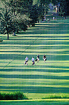 Golfers walk down the fairway on a summer evening in Missoula, Montana