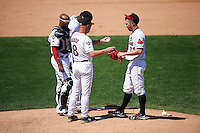 Rochester Red Wings manager Mike Quade (8) hands the ball to relief pitcher Sean Burnett (21) as catcher Carlos Paulino (17) and third baseman Miguel Sano (9) look on during a game against the Pawtucket Red Sox on June 29, 2016 at Frontier Field in Rochester, New York.  Pawtucket defeated Rochester 3-2.  (Mike Janes/Four Seam Images)