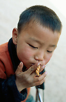 China. Province of Shaanxi. Village Shifeng. Li Hupeng is the boy's name. He was kidnapped on may 12 2002, sold to a family in the village of Xiaotan in Henan province. The police found him and brought him back to his family on march 4 2004. Li Hupeng pretends to smoke a cigarette, using a cracker, in the courtyard of his house. © 2004 Didier Ruef