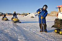 Volunteer drills hole in ice to put in wood stake trail markers on Unalakleet River near Unalakleet