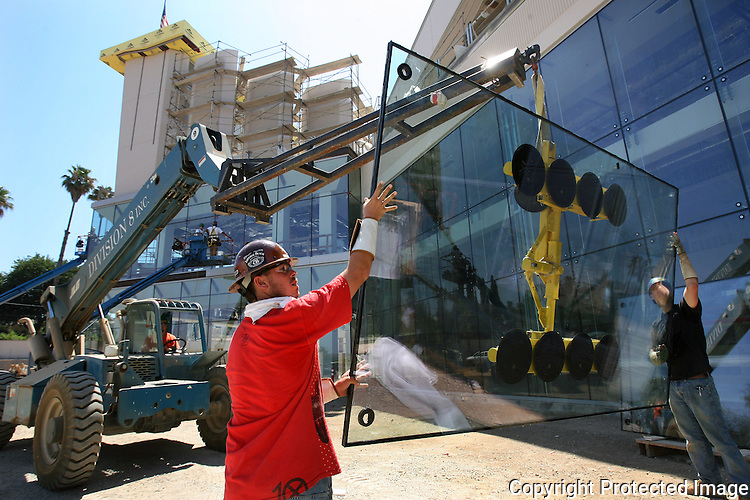 Glass workers steady a sheet of glass for installation at a Lexus dealership under construction in Escondido, California, in 2009.  photo for North County Times