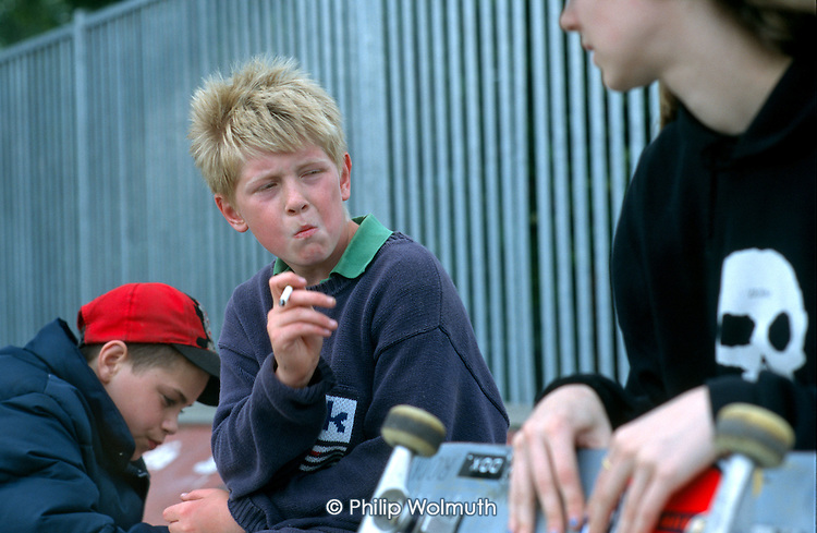 12 year old boy smoking a cigarette in a park in Camden, London