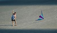 A man flies a kite in afternoon shadows at Virginia Beach, Va.
