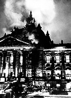 """Firemen work on the burning Reichstag Building in February 1933, after fire broke out simultaneously at 20 places.  This enabled Hitler to seize power under the pretext of """"protecting"""" the country from the menace to its security.  Berlin.  Acme.  (OWI)<br /> Exact Date Shot Unknown<br /> NARA FILE #:  208-N-39835<br /> WAR & CONFLICT BOOK #:  987"""