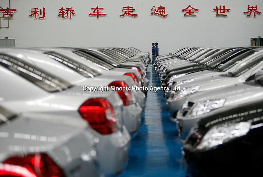 """Workers at the Geely Automobiles Factory in Taizhou, Zhejiang Province, China. The characters on the wall says: """"Geely sedans walk all over the world"""". Geely's profit rose 88 percent in 2006 as it sold more mid-range cars.."""